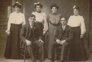 Tom is seated on the left, pictured with his sisters and brother.